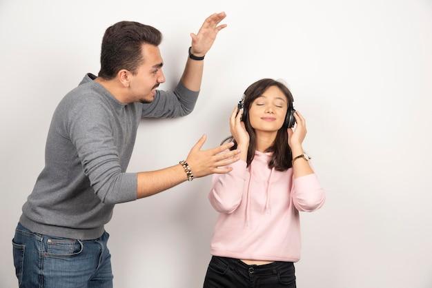 Młody mężczyzna stara się zwrócić na siebie uwagę młodej kobiety.