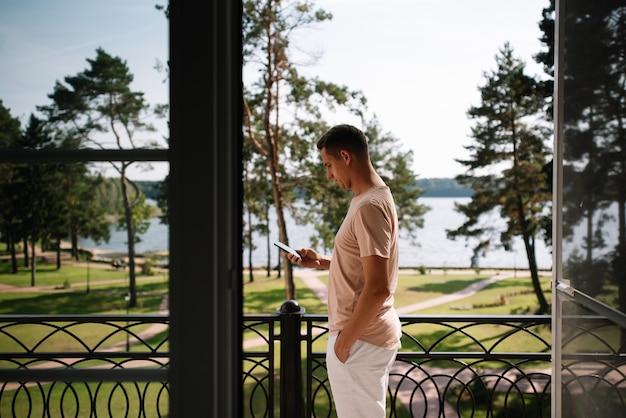 Młody mężczyzna stoi na balkonie i patrzy na swój telefon na tle natury
