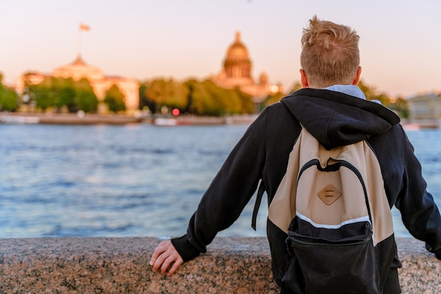 Młody mężczyzna stoi na nasypie w petersburgu o zachodzie słońca