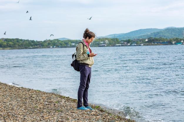Młody mężczyzna stoi na plaży i patrzy w telefon.