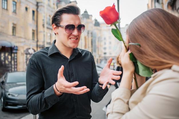 Młody mężczyzna stoi przed kobietą i rozmawia z nią. w rękach trzyma czerwoną różę. facet nosi okulary przeciwsłoneczne.