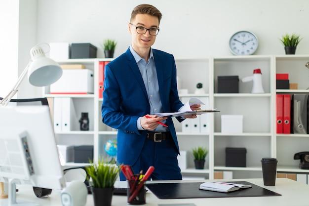 Młody mężczyzna stoi przy stole w biurze i trzyma długopis i dokumenty.