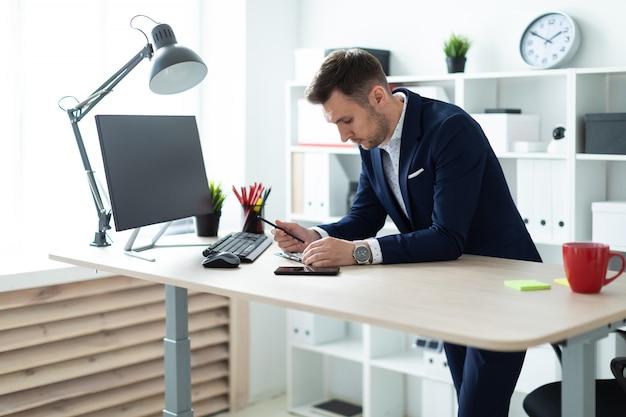 Młody mężczyzna stoi przy stole w biurze, trzyma w ręce ołówek i pracuje z dokumentami i komputerem.