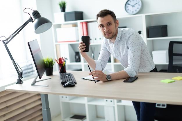 Młody mężczyzna stoi przy stole w biurze, trzymając ołówek i szklankę kawy. młody człowiek pracuje z dokumentami i komputerem.