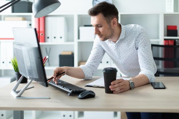 Młody mężczyzna stoi przy stole w biurze, trzymając ołówek i szklankę kawy.