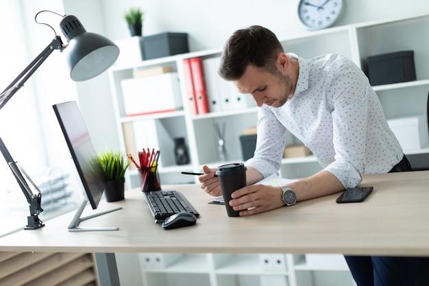 Młody mężczyzna stoi przy stole w biurze, trzymając ołówek i szklankę kawy