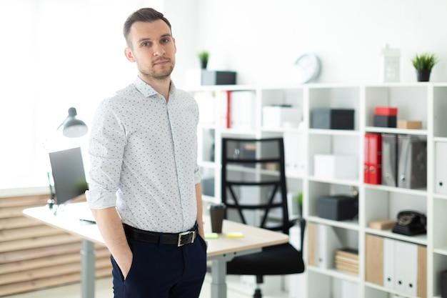 Młody mężczyzna stoi przy stole w biurze, z rękami w kieszeniach.