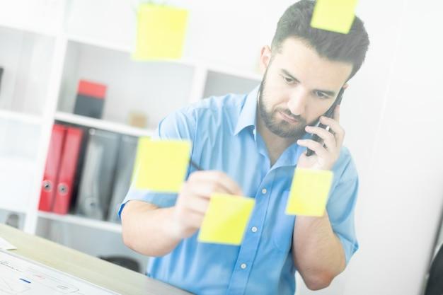 Młody mężczyzna stoi w biurze przy przezroczystej tablicy z naklejkami.