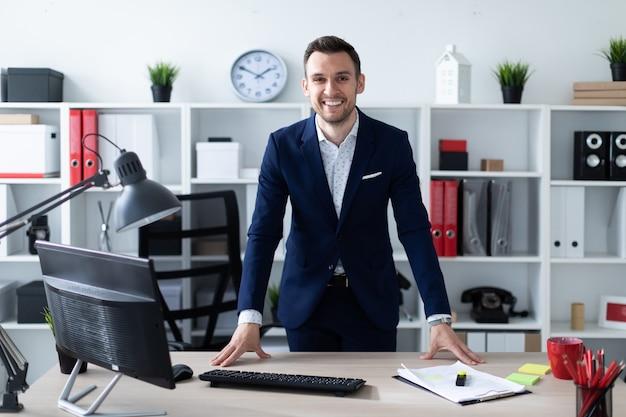 Młody mężczyzna stoi w biurze przy stole i kładzie na nim ręce.