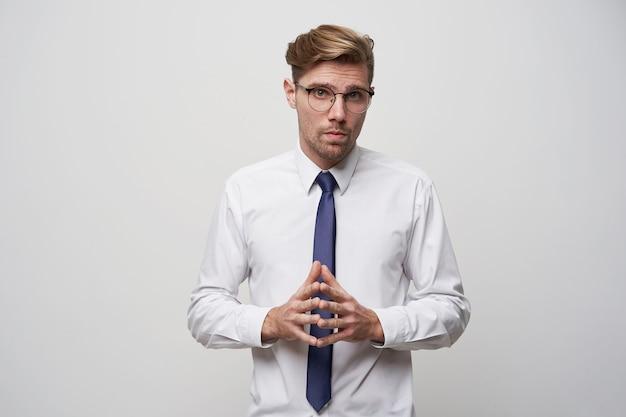 Młody mężczyzna stoi ze złożonymi z przodu palcami