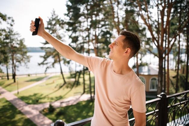 Młody mężczyzna stojący na balkonie robi selfie telefonem komórkowym