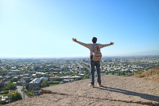 Młody mężczyzna stojący na skraju wzgórza otwierając ramiona z imponującym widokiem na miasto