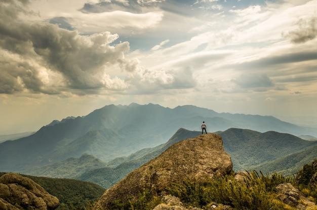 Młody mężczyzna stojący na szczycie wzgórza pod zachmurzonym błękitnym niebem