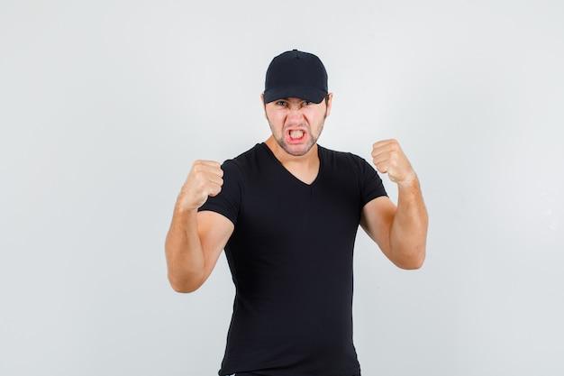 Młody mężczyzna stojący na w pozie boksera w czarnej koszulce