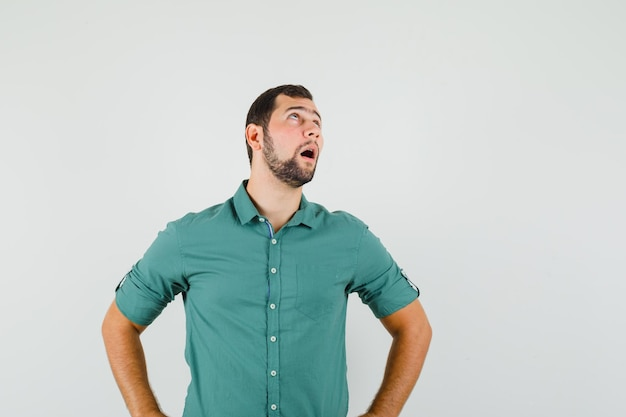Młody mężczyzna stojący patrząc na bok w zielonej koszuli i patrząc znudzony. przedni widok.