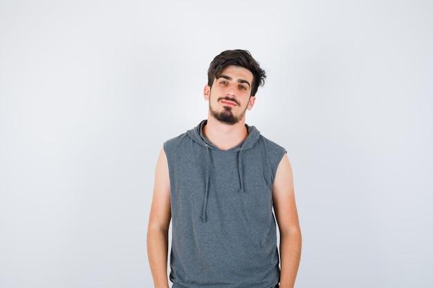 Młody mężczyzna stojący prosto i pozujący do kamery w szarym t-shircie i wyglądający poważnie