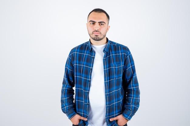 Młody mężczyzna stojący prosto i trzymający się za ręce w kieszeni w kraciastej koszuli i białej koszulce i patrzący poważnie