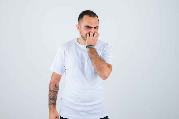 Młody mężczyzna stojący prosto, kładący rękę na ustach w białej koszulce i czarnych spodniach i wyglądający na zaskoczonego