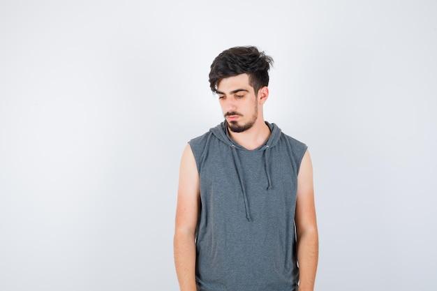 Młody mężczyzna stojący prosto, odwracający wzrok i pozujący do kamery w szarej koszuli i patrzący zamyślony