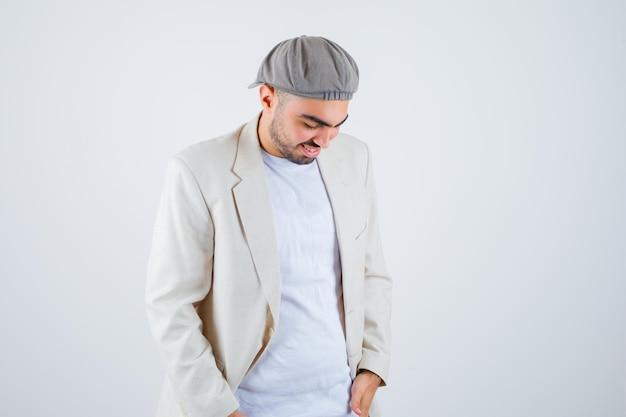 Młody mężczyzna stojący prosto, patrzący w dół i pozujący z przodu w białej koszulce, kurtce i szarej czapce i wyglądający na szczęśliwego