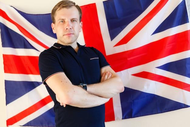Młody mężczyzna stojący przed flagą wielkiej brytanii