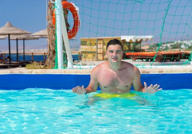 Młody mężczyzna stojący przy bramie w basenie grający w piłkę wodną w hotelu w słoneczny letni dzień