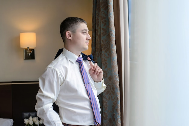 Młody mężczyzna stojący przy oknie