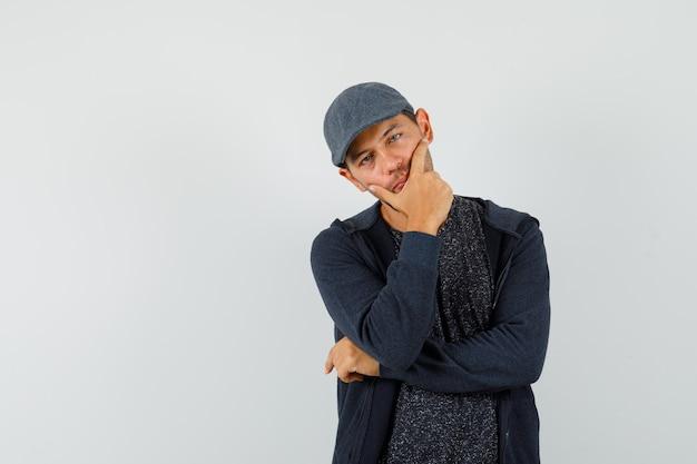 Młody mężczyzna stojący w myślącej pozie w koszulce, kurtce, czapce i spokojnym spojrzeniu. przedni widok.