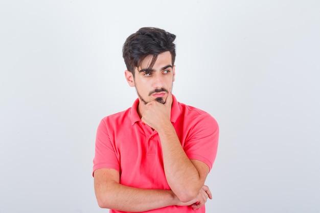 Młody mężczyzna stojący w myśleniu pozie w t-shirt i wyglądający rozsądnie, widok z przodu.