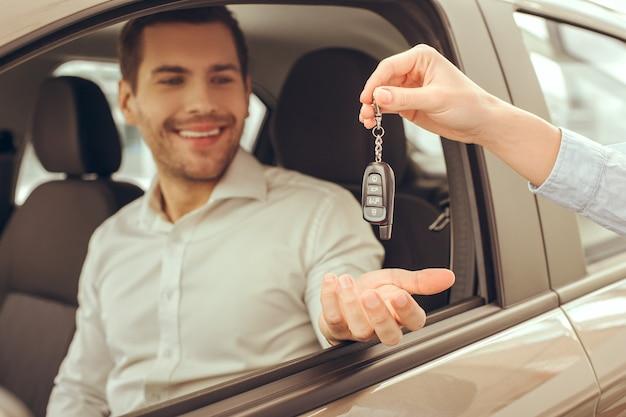 Młody mężczyzna stojący w pobliżu samochodu i wypożyczający klucze