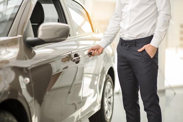 Młody mężczyzna stojący w pobliżu wypożyczalni samochodów otwierających drzwi