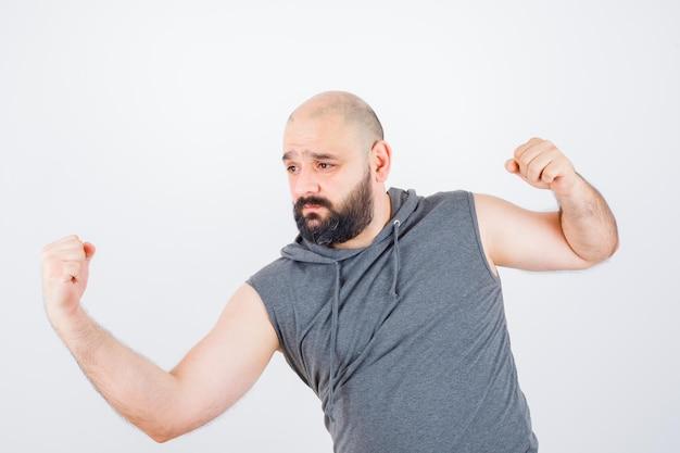 Młody mężczyzna stojący w pozie do walki w bluzie z kapturem bez rękawów i wyglądający na złośliwego. przedni widok.