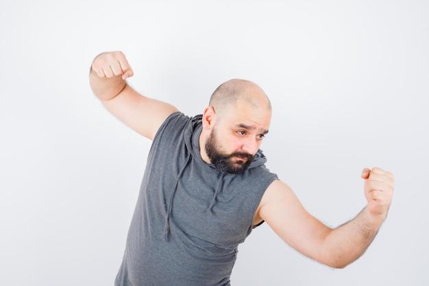 Młody mężczyzna stojący w pozie do walki w bluzie z kapturem bez rękawów i wyglądający pewnie. przedni widok.