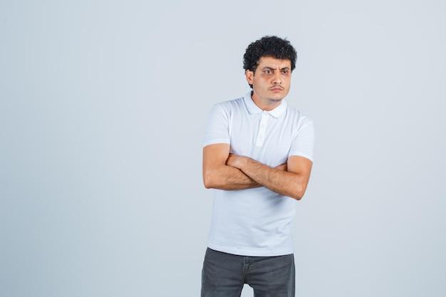 Młody mężczyzna stojący ze skrzyżowanymi rękami w białej koszulce, spodniach i patrząc zamyślony, widok z przodu.