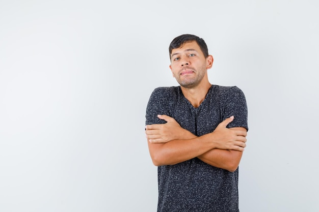 Młody mężczyzna stojący ze skrzyżowanymi rękami w czarnej koszulce i patrząc zamrożony. przedni widok. miejsce na tekst
