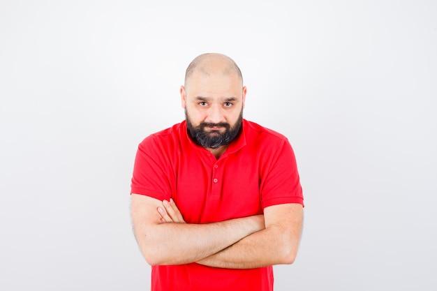 Młody mężczyzna stojący ze skrzyżowanymi rękami w czerwonej koszuli i patrząc na spokój. przedni widok.