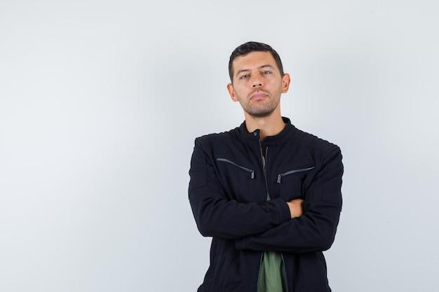Młody mężczyzna stojący ze skrzyżowanymi rękami w koszulce, kurtce i patrząc pewnie, widok z przodu.