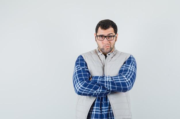 Młody mężczyzna stojący ze skrzyżowanymi rękami w koszuli, kurtce, okularach i patrząc ostrożnie. przedni widok.