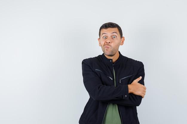 Młody mężczyzna stojący ze skrzyżowanymi rękami, zakrzywione usta w koszulce, kurtce i patrząc zamyślony, widok z przodu.