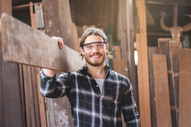 Młody mężczyzna stolarz pracownik uśmiecha się trzymając drewnianą deskę w warsztacie stolarskim
