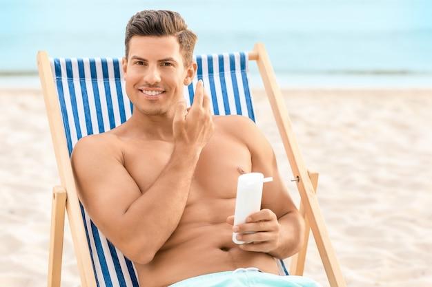 Młody mężczyzna stosujący krem przeciwsłoneczny na morskiej plaży