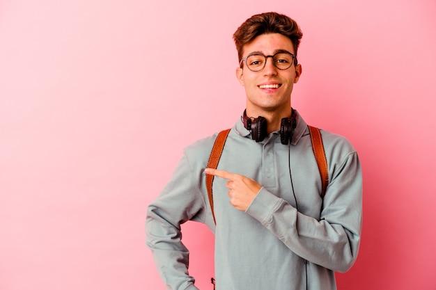 Młody mężczyzna student samodzielnie na różowym tle, uśmiechając się i wskazując na bok, pokazując coś w pustej przestrzeni.