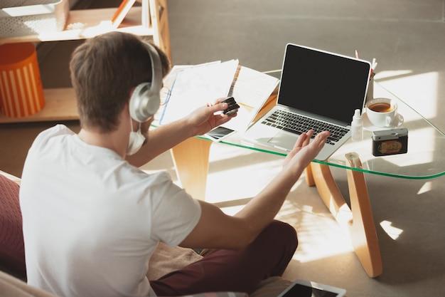 Młody mężczyzna studiuje w domu podczas kursów online dla fotografa, asystenta studia.