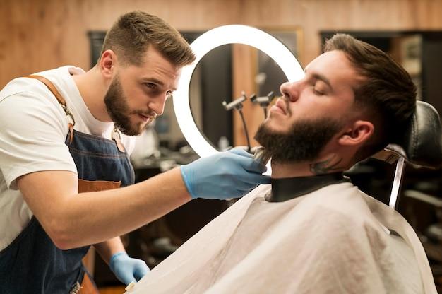 Młody mężczyzna stylizujący brodę u fryzjera