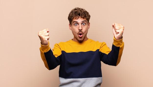 Młody mężczyzna świętujący niewiarygodny sukces jak zwycięzca, wyglądający na podekscytowanego i szczęśliwego, mówiąc: weź to!