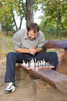Młody mężczyzna szachista siedzi okrakiem na siedzeniu wiejskiej drewnianej ławce zgarbiony nad szachownicą planując swoją strategię
