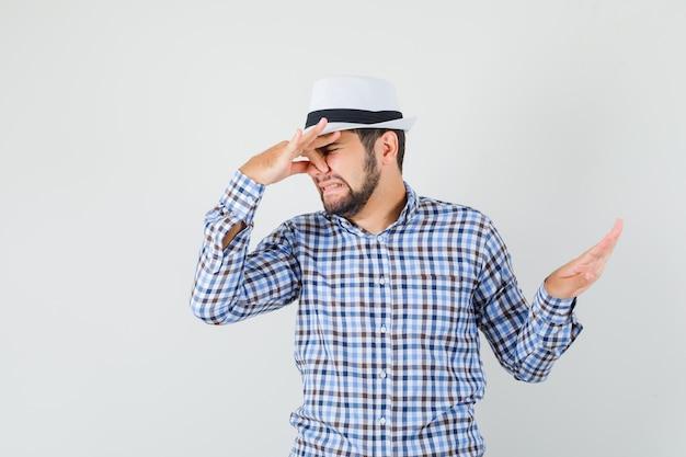 Młody mężczyzna szczypie nos z powodu nieprzyjemnego zapachu kraciastej koszuli, kapelusza i wyglądającego na zniesmaczonego, widok z przodu.