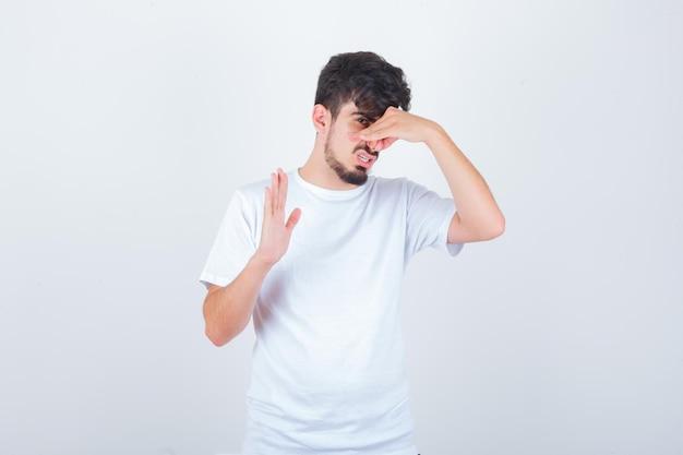 Młody mężczyzna szczypie nos z powodu nieprzyjemnego zapachu w koszulce i wygląda na zdegustowanego