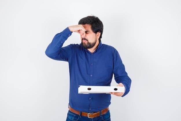 Młody mężczyzna szczypie w nos z powodu nieprzyjemnego zapachu w koszuli, dżinsach i wygląda na zdegustowanego. przedni widok.