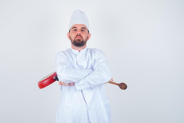 Młody mężczyzna szef kuchni trzyma patelnię i drewnianą łyżkę, stojąc ze skrzyżowanymi rękami w białym mundurze i patrząc pewnie, widok z przodu.